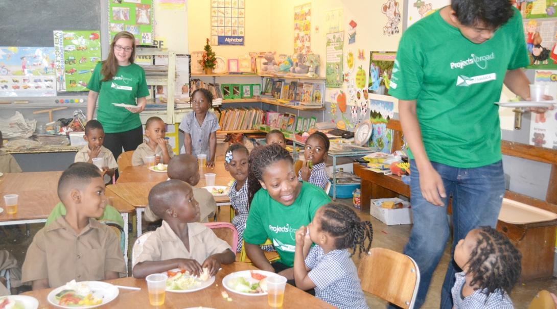 ジャマイカの幼稚園で昼食の時間の補助を行うチャイルドケアボランティア